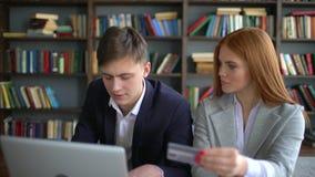 Jonge het glimlachen paarzitting op laag en het gebruiken van laptop en creditcard voor het inkopen van Internet de Man en de vro stock videobeelden