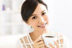 Jonge het glimlachen vrouw het drinken koffie in de ochtend Stock Afbeelding