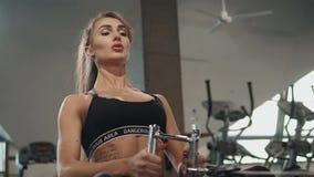Jonge het meisjesatleet die van de sportvrouw harde training op het roeien machines in gymnastiek hebben Donkerbruin sexy mooi ge stock videobeelden