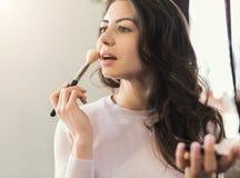 Jonge het poederstichting van de vrouwenmake-up in salon stock fotografie