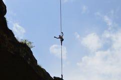 Jonge highliner die hoog op een strak koord in de hemel lopen Royalty-vrije Stock Foto's