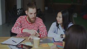 Jonge hipsermens in binnen het spreken over nieuw startproject met vrouwelijk en mannelijk multi etnisch team in zolderbureau stock video
