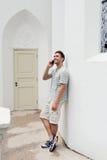 Jonge hipster die een telefoongesprek in openlucht maken stock fotografie