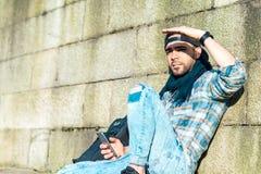 Jonge hipster die mobiele telefoon in openlucht met behulp van stock afbeeldingen