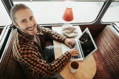 Jonge hipster mannelijke zitting met laptop in buskoffie stock afbeeldingen