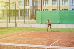 Jonge hipster op het hof de toevallige tennisspeler stock afbeelding