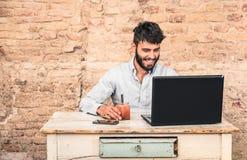 Jonge hipsterkerel met snorzitting bij laptop Stock Foto's