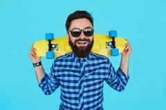 Jonge hipstermens met een skateboard Royalty-vrije Stock Afbeeldingen