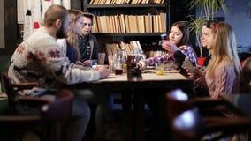Jonge hipsters die bij koffie lijst en het spreken zitten stock video
