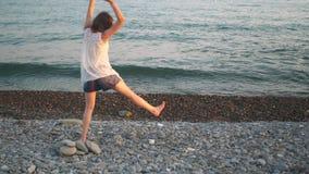 Jonge hipstervrouw die cartwheel op strand bij zonsondergang doen stock video