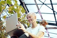 Jonge hipstervrouw met blonde kort haar die en aan laptop, die aan treden glimlachen werken zitten Binnen botanisch tuinbinnenlan royalty-vrije stock afbeeldingen