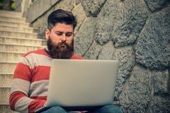 Jonge hipsterzitting en het gebruiken van laptop Stock Fotografie