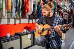 Jonge hipsterzitting en het spelen op akoestische gitaar Hij kijkt neer De kerel is geconcentreerd Vele elektronische gitaren en royalty-vrije stock afbeeldingen