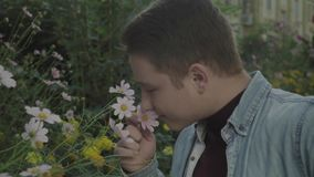 Jonge homosexueel die van de geur van bloemen genieten stock videobeelden
