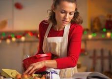 Jonge huisvrouw die Kerstmisdiner in keuken voorbereidt Stock Afbeeldingen