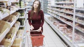 Jonge huisvrouw die met karretje bij de kruidenierswinkelopslag winkelen stock videobeelden