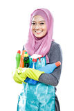 Jonge huisvrouw die vele flessen schoonmakende vloeistof dragen Stock Foto's