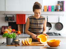 Jonge huisvrouwen scherpe pompoen in keuken Stock Fotografie
