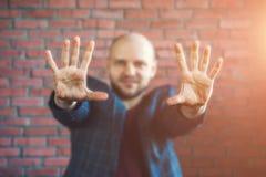 Jonge hypnotiseur of zakenman in een jasje die en handen vooruit uitgestrekt met palmen glimlachen tonen royalty-vrije stock afbeelding