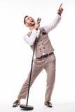 Jonge impresario in kostuum het zingen met emoties en gericht gebaar over de microfoon met energie stock foto