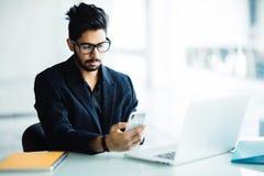 Jonge Indische CEO die van bedrijf in zijn bedrijfsbureau bij bureau, tekst op smartphone lezen royalty-vrije stock afbeeldingen