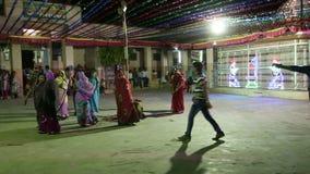 Jonge Indische vrouwen die bij straat in Jodhpur, met mannen dansen die hen naderen stock footage