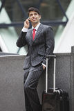 Jonge Indische zakenman die op celtelefoon communiceren terwijl status naast bagagezak Stock Foto's