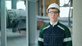 Jonge ingenieur die het beschermende helm stellen dragen die camera bij moderne fabriek bekijken stock videobeelden