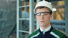 Jonge ingenieur die het beschermende helm stellen dragen die camera bij moderne fabriek bekijken stock video