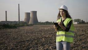 Jonge ingenieursvrouw verantwoordelijk met het werkveiligheid het inspecteren bij de plaatsbouw die nota's over industriële activ stock footage