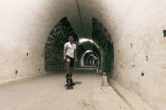 Jonge jaar 20-25 oude mens in tunnel met skateboard Omringende lig royalty-vrije stock afbeeldingen