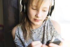 Jonge 10 jaar vrouw het luisteren muziek dicht bij het venster royalty-vrije stock foto