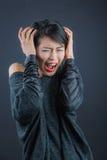 Jonge Japanse die dame door hevig slecht lawaai wordt gekwetst stock fotografie
