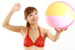 Jonge Japanse vrouw die bikini met strandbal dragen Royalty-vrije Stock Foto's