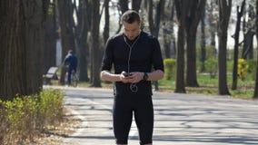 Jonge jogger die aan muziek met smartphone en handen vrije oortelefoons luisteren die voor het texting pauzeren stock videobeelden