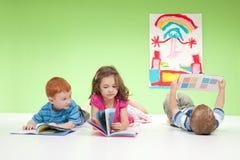 Jonge jonge geitjes die boeken lezen Stock Foto