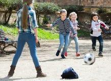 Jonge jonge geitjes die straatvoetbal in openlucht spelen Stock Afbeeldingen