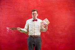 Jonge jonge grappige mens met bloemen en gift Stock Afbeeldingen
