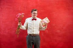 Jonge jonge grappige mens met bloemen en gift Stock Foto