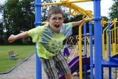 Jonge jongen bij de speelplaats Stock Foto's