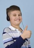 Jonge jongen die aan muziek op hoofdtelefoons luistert stock foto's