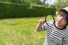 Jonge jongen die aard in de weide met een vergrootglas onderzoeken die bloemen bekijken Nieuwsgierige kinderen in het hout, een b stock afbeeldingen