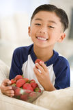 Jonge jongen die aardbeien in woonkamer eet Stock Foto's