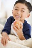 Jonge jongen die appel in woonkamer eet royalty-vrije stock afbeelding