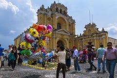 Jonge jongen die baloons in een straat van de oude stad van Antigua met San Pedro Hospital op de achtergrond, in Guatemala verkop Royalty-vrije Stock Afbeelding