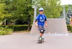 Jonge jongen die bij het park met een skateboard rijden royalty-vrije stock afbeelding