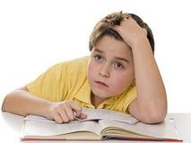 Jonge jongen die bij thuiswerk droomt Stock Foto's