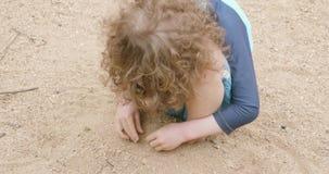 Jonge jongen die blauwe swimwear dekking zijn voeten met zand op een strand dragen stock video