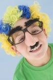Jonge jongen die clownpruik en valse neus draagt Royalty-vrije Stock Foto's