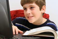 Jonge jongen die computer witte achtergrond gebruikt royalty-vrije stock foto